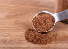 Ground Allspice on a Wooden Table. Closeup of ground allspice and measuring spoon on a wooden table with copy space royalty free stock image