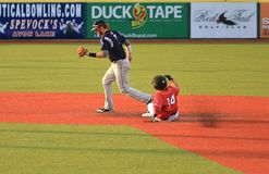 Ground ball. Runner extends his leg in an attempt to beat the throw at second royalty free stock images