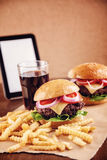 Ground beef Cheese Burger with French Fries and Cola. Ground beef Cheese Burger with Lettuce,Tomato and Red Onion with French Fries and glass of Cola Royalty Free Stock Image