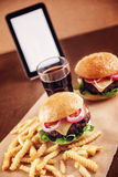 Ground beef Cheese Burger with French Fries and Cola. Ground beef Cheese Burger with Lettuce,Tomato and Red Onion with French Fries and glass of Cola Royalty Free Stock Photography