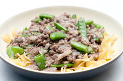 Ground beef hamburger stroganoff with chopped snap peas and broa Royalty Free Stock Photos