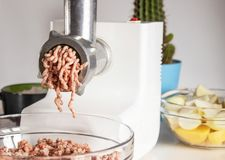 Ground beef is ground in a meat grinder, the ingredients are in a bowl stock photography