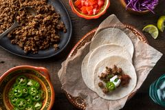 Ground Beef Tacos. Delicious ground beef tacos with jalapeno pepper, salsa, cilantro, sour cream, and lime royalty free stock photos