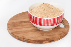 Ground biscuits for preparing cake in white bowl on wooden board Stock Photography