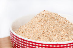 Ground biscuits for preparing cake in white bowl on wooden board Royalty Free Stock Images
