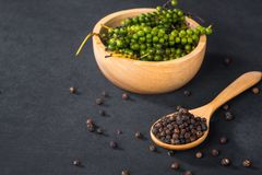 Ground black pepper. Close-up of ground black pepper in wooden spoon on black table royalty free stock image