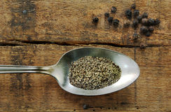 Ground Black Pepper and Peppercorns. Ground black pepper in a spoon with peppercorns on a rustic wood table stock photos