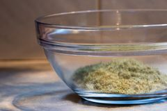 Ground cannabis flower in a clear glass bowl. Processed herb in preperation for making marijuana tincture Stock Photography