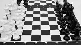 Ground chess and checker board. This is a black and white picture. A set of chess and checker board are placed on ground. Numbers are clearly labeled. It is a stock image
