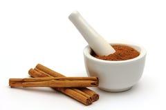 Ground cinnamon in a bowl with cinnamon sticks Stock Photos
