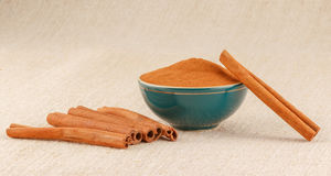 Ground cinnamon in bowl and cinnamon sticks. Ground cinnamon powder in green porcelain bowl and cinnamon sticks on rustic table cloth royalty free stock photo