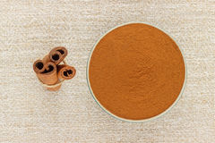 Ground cinnamon in bowl and cinnamon sticks. Ground cinnamon powder in porcelain bowl and cinnamon sticks on rustic table cloth, seen from above Stock Photography