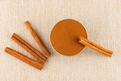 Ground cinnamon in bowl and cinnamon sticks. Ground cinnamon powder in porcelain bowl and cinnamon sticks on rustic table cloth, seen from above Stock Image