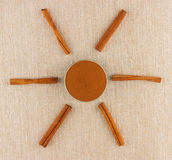 Ground cinnamon in bowl and cinnamon sticks. Ground cinnamon powder in porcelain bowl and cinnamon sticks on rustic table cloth, seen from above Royalty Free Stock Photography