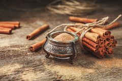 Ground cinnamon, cinnamon sticks, tied with jute rope on old wooden background in rustic style. Ground cinnamon, cinnamon sticks, tied with jute rope on old royalty free stock photography