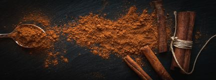 Ground cinnamon in teaspoon, and cinnamon sticks on dark background, top view, text space royalty free stock photos