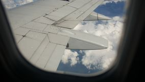 Ground and clouds under wing of an airplane during flight stock video