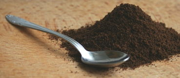 Ground coffee. Grounded coffee and a silver spoon on a brown desk Royalty Free Stock Photo