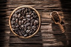 Ground coffee beans bowl scoop on wooden board.  stock images