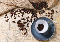Ground coffee. Blue ceramic cup with ground coffee and roasted coffe beans over old newspaper. Top view stock images