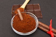 Ground coffee and chocolate on the background and fresh piled coffee on wooden spoon Royalty Free Stock Photo