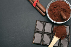 Ground coffee and chocolate on the black background and fresh piled coffee on wooden spoon Stock Photo