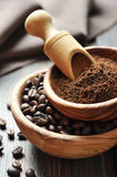 Ground coffee and coffee beans. In bowls on wooden background stock photo