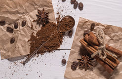 Ground coffee, coffee beans, silver spoon, bunch of cinnamon Stock Photos