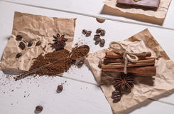Ground coffee, coffee beans, silver spoon, bunch of cinnamon Royalty Free Stock Images