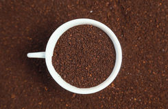 Ground coffee in a cup. White cup filled with ground coffee on a background coffee royalty free stock images