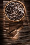 Ground coffee grains bowl scoop on vintage wooden board.  royalty free stock images