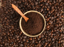 Ground coffee and grains. Cup filled with ground coffee on a background grains royalty free stock image