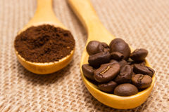 Ground coffee and grains with wooden spoon on jute canvas Royalty Free Stock Photos