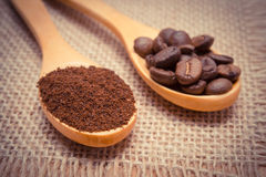 Ground coffee and grains with wooden spoon on jute canvas Royalty Free Stock Image