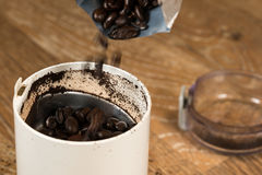 Ground coffee in grinder on wooden table Stock Photos