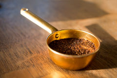 Ground coffee in measuring cup. In the morning sunlight Royalty Free Stock Images