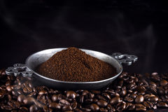 Ground coffee in a metal cup on freshly roasted coffee beans aga Royalty Free Stock Images