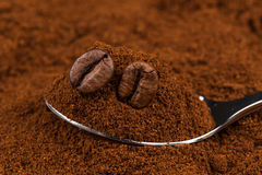 Ground coffee and a metal spoon Stock Images
