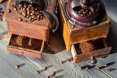 Ground coffee in the old-fashioned grinders. On old wooden table stock photo