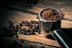 Ground coffee in porta filter holder. On the wooden surface with beans dropped loosely Royalty Free Stock Image