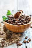 Ground coffee and roasted coffee beans in a wooden bowl. Royalty Free Stock Photos