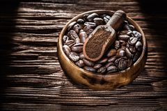 Ground coffee seeds bowl scoop on wooden board.  stock images