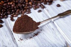 Ground coffee in spoon with coffee beans. Stock Image