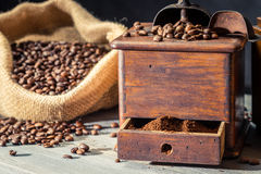 Ground coffee in vintage grider and beans in sack Royalty Free Stock Photography