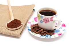 Ground coffee on wooden scoop and cup of hot beverage Stock Photo