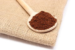Ground coffee on wooden scoop lying on jute fabric Royalty Free Stock Photography