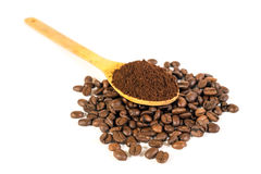Ground coffee on wooden spoon. Lots of coffee beans scattered on Royalty Free Stock Image