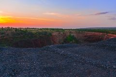 Ground collapse behind the dump. A landscape of sunset sky over the ground collapse. Worked out iron ore breed wide landscape. Kriviy Rih. Ukraine. Excavation of royalty free stock image