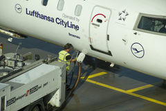 Ground crew refueling a passenger Lufthansa airplane. Stock Photography