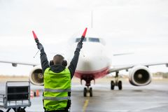 Ground Crew Signaling To Airplane On Runway. Rear view of ground crew signaling to airplane on wet runway Royalty Free Stock Photography